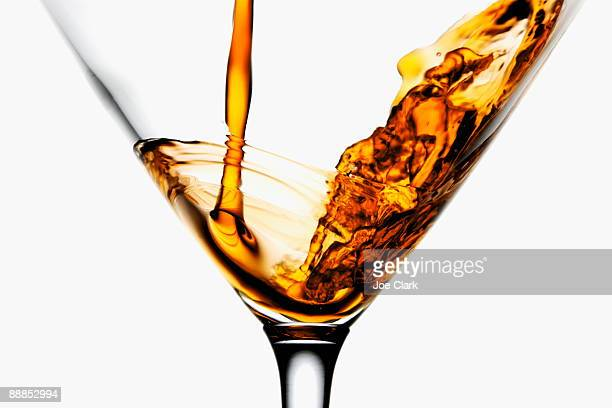 Drink being poured into wineglass, close-up