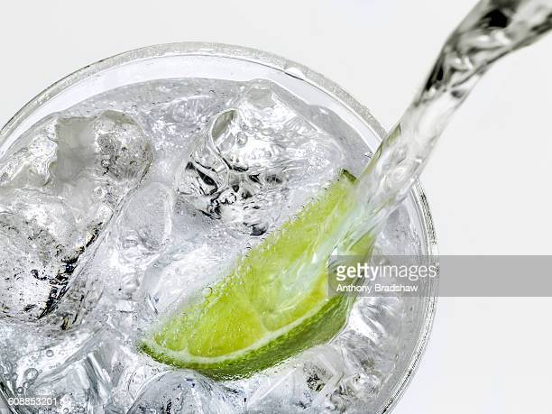 Drink being poured over ice and lime