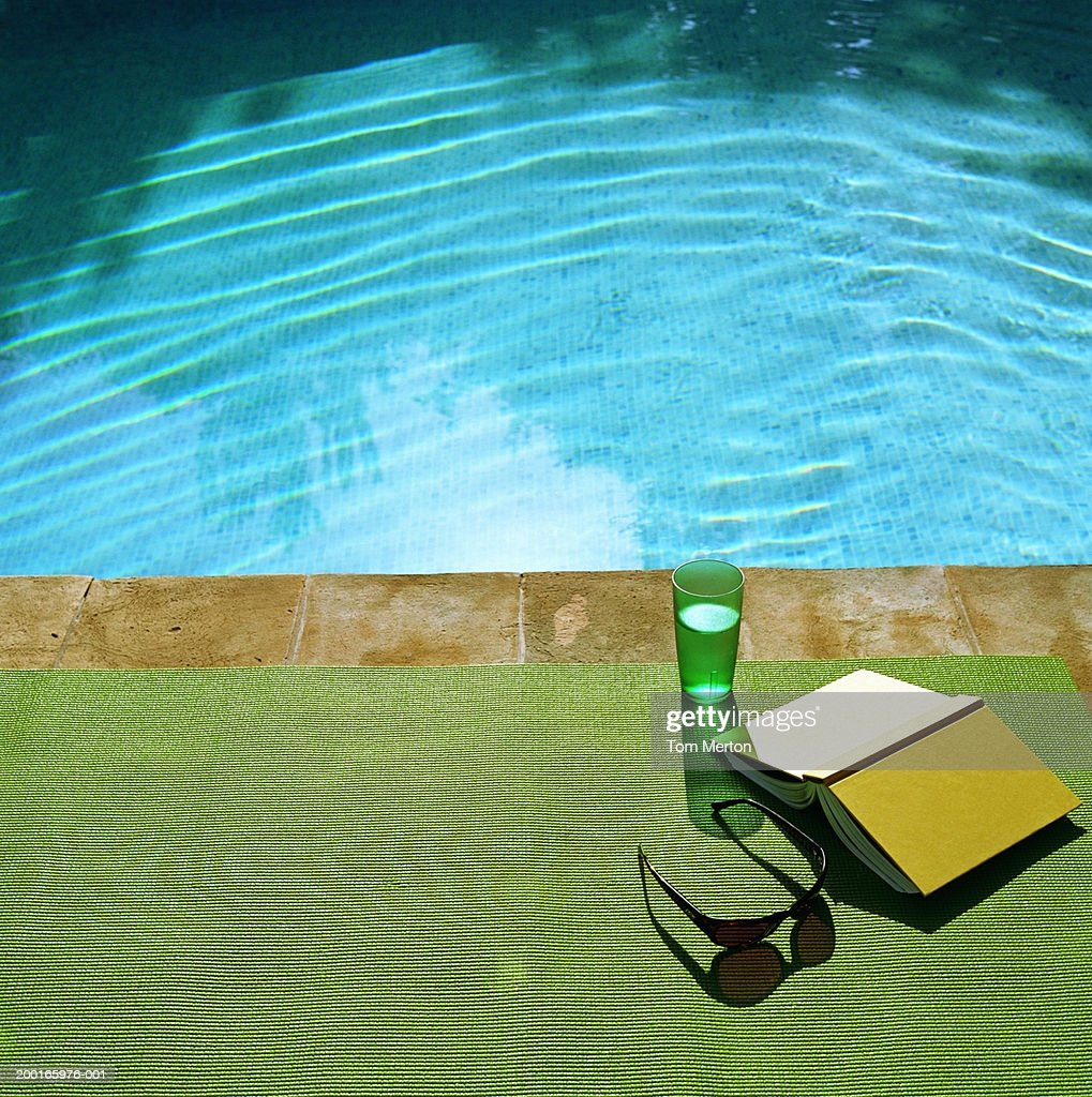 drink book and sunglasses on beach mat at edge of swimming pool