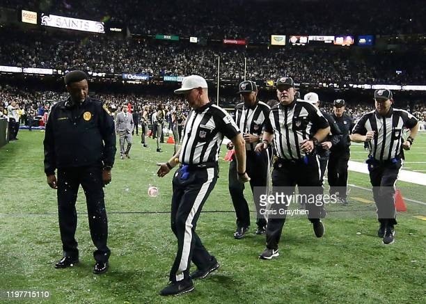 A drink is thrown at referees as they leave the field after the NFC Wild Card Playoff game between the Minnesota Vikings and the New Orleans Saints...