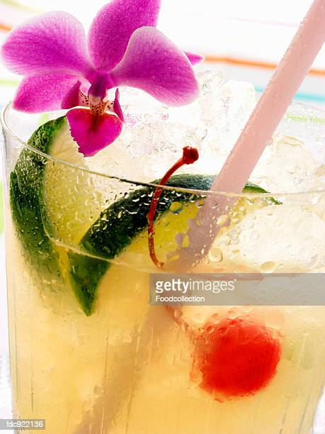 drink with lime, ice, cocktail cherry and orchid - garnish stock pictures, royalty-free photos & images