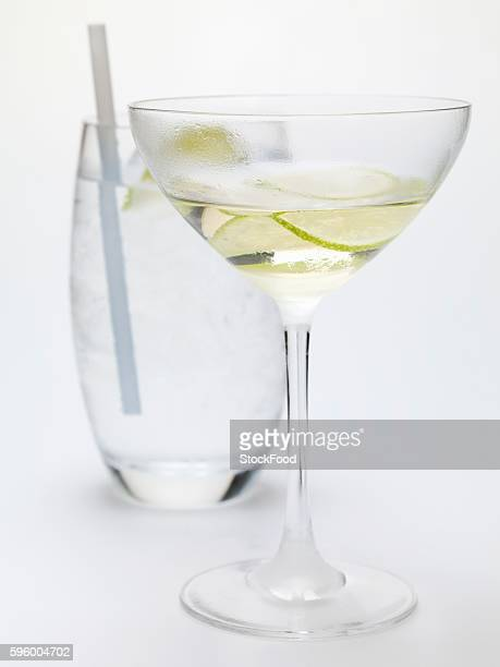 Drink with slices of lime, glass of water in background