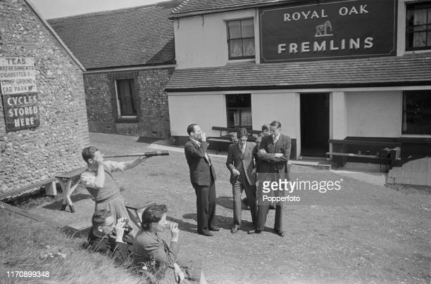 Drinkers at the Royal Oak public house observing a dogfight between planes from the Royal Air Force and the Luftwaffe over the English Channel during...