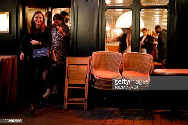 Drinkers leave a bar in Soho, in central London on September 24 on the first day of the new earlier closing times for pubs and bars in England and...