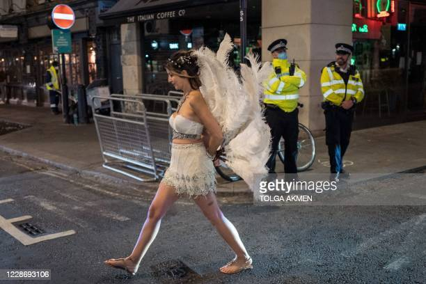 TOPSHOT Drinkers leave the bars as police patrol in Soho in central London on September 24 2020 as the clock nears 10pm on the first day of the new...