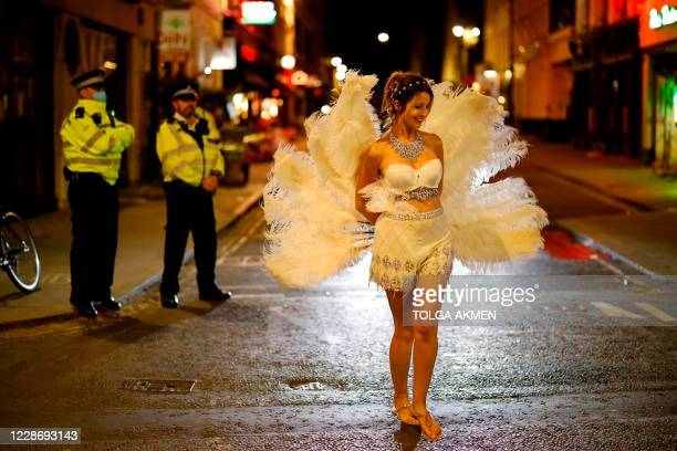 Drinkers leave the bars as police patrol in Soho in central London on September 24 2020 as the clock nears 10pm on the first day of the new earlier...