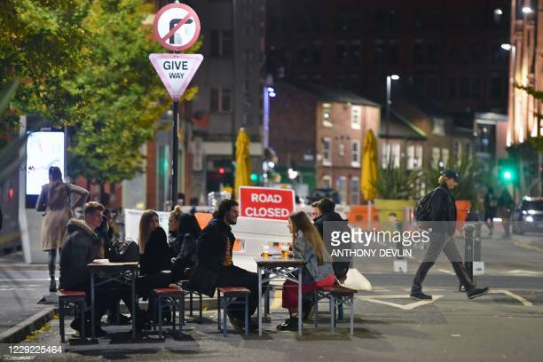 Drinkers outside a bar on Thomas Street in Manchester city centre northwest England ahead of new coronavirus restrictions coming into force on...
