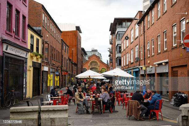Drinkers sit at outdoor seating provided by adjacent bars on a road closed to facilitate Covid-safe socialising in central Manchester on August 30,...