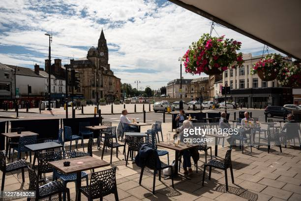 Drinkers sit outside a pub in Rochdale in Rochdale, greater Manchester, northwest England on July 30, 2020. - Rochdale reportedly faces harsher...