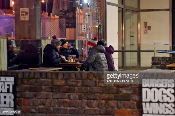 Drinkers sit outside Brewdog in Manchester city centre northwest England ahead of new coronavirus restrictions coming into force on October 22 2020...