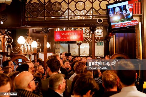 TOPSHOT Drinkers watch a television screen in the Red Lion public house on Whitehall as it shows Britain's Prime Minister Theresa May speaking in the...