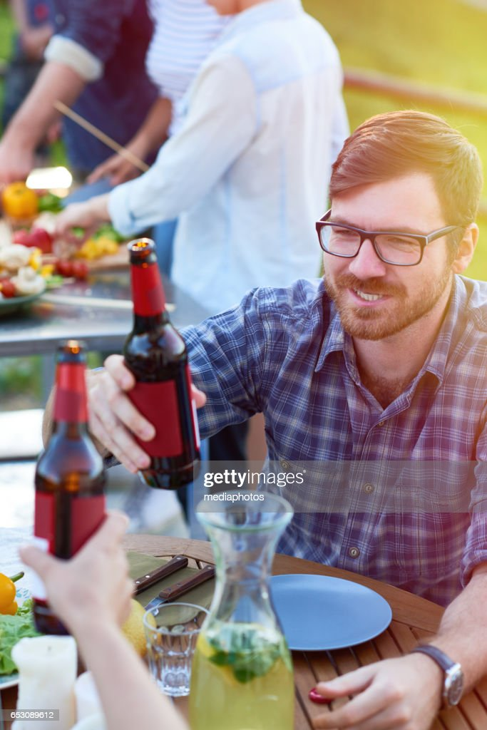Drinking beer at garden party : Foto stock