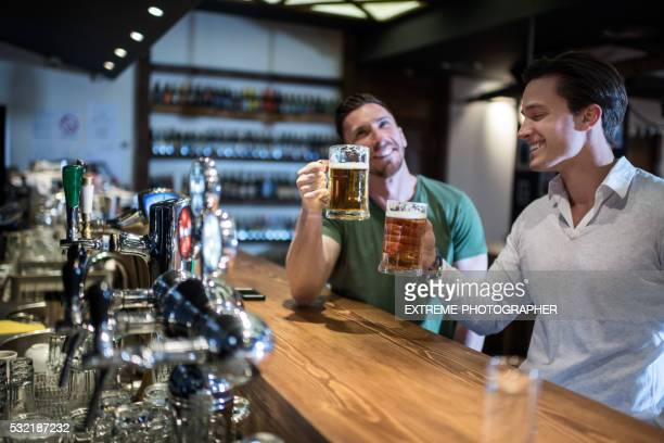 drinking beer in the pub - irish pub stock photos and pictures