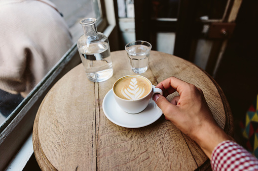 Drinking cappuccino with latte art in coffee shop, personal perspective view - gettyimageskorea