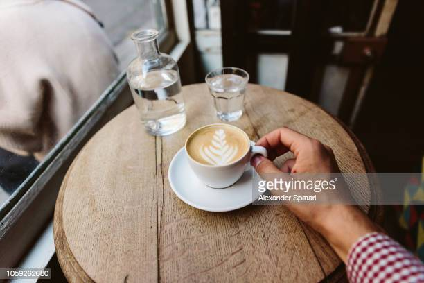Drinking cappuccino with latte art in coffee shop, personal perspective view