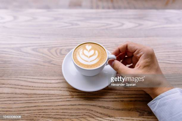 Drinking coffee at the bar counter in coffee shop, personal perspective