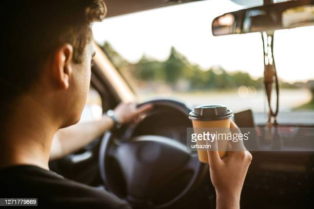drinking coffee during car drive - on the move stock pictures, royalty-free photos & images