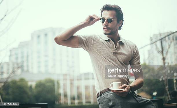 drinking coffee in the city - polo shirt stock pictures, royalty-free photos & images