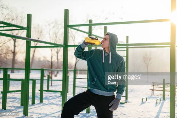 drinking energy drink on winter training - energy drink stock pictures, royalty-free photos & images