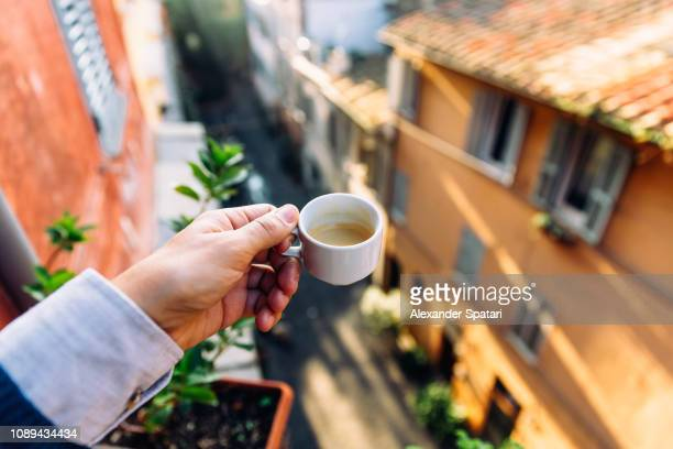 drinking espresso on the balcony in rome, personal perspective view - italy stock-fotos und bilder