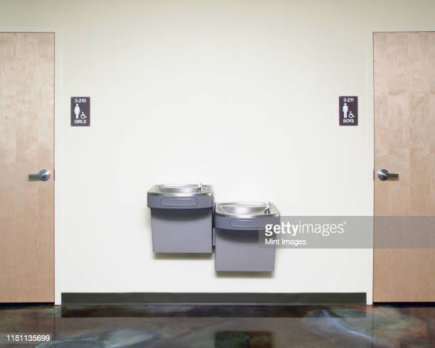 drinking fountains near restroom - fountain stock pictures, royalty-free photos & images