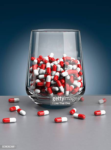 A drinking glass filled with pills