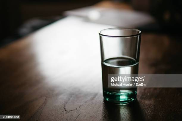 drinking glass on table - half full stock photos and pictures