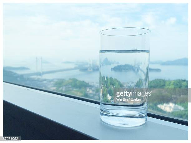 Drinking Glass On Window Sill By Sea Against Sky