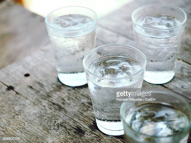 drinking glasses on wooden table - trinkwasser stock-fotos und bilder
