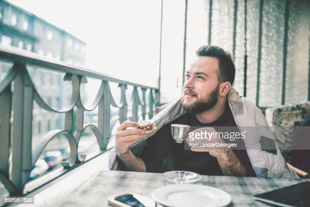 Seine morgendlichen Kaffee zu trinken und Essen Donut auf Balkon