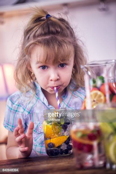 drinking infused water with fresh blueberries and oranges - infused water stock pictures, royalty-free photos & images