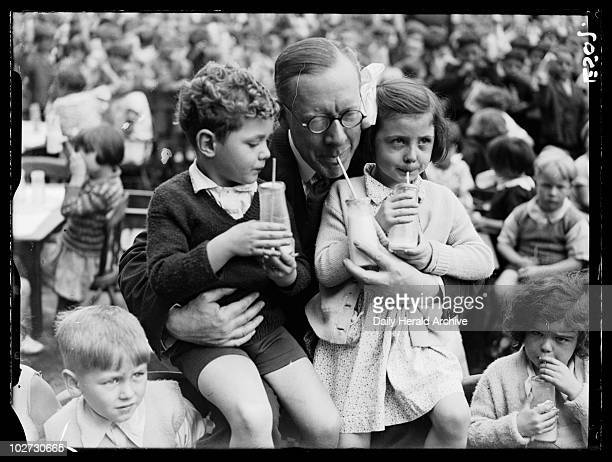 Drinking milk 1934 A photograph of Major Elliot Minister of Agriculture lifting up two children in his arms taken by Woodbine for the Daily Herald...
