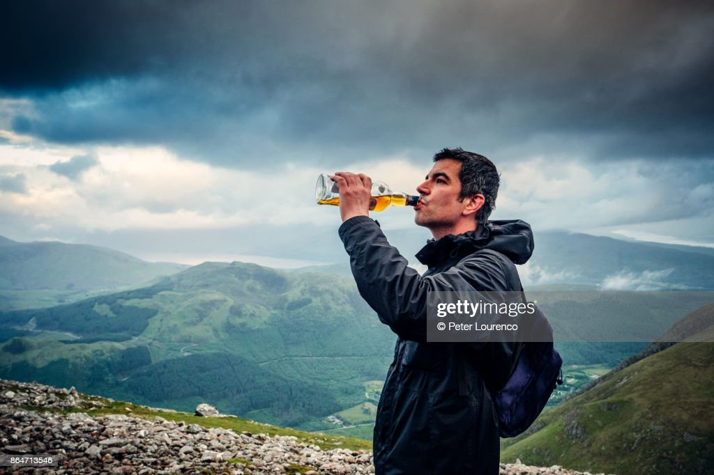 Drinking Scotch from the bottle on Ben Nevis : Stock Photo