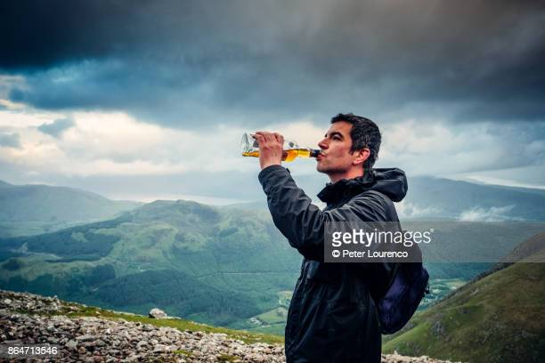 drinking scotch from the bottle on ben nevis - scotland stock pictures, royalty-free photos & images