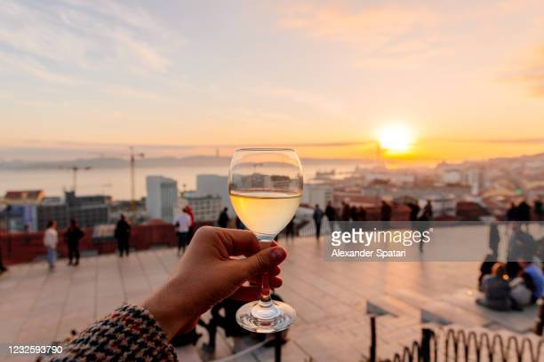 drinking vinho verde (green wine) with view of lisbon skyline at miradouro de santa catarina, portugal - provincie lissabon stockfoto's en -beelden