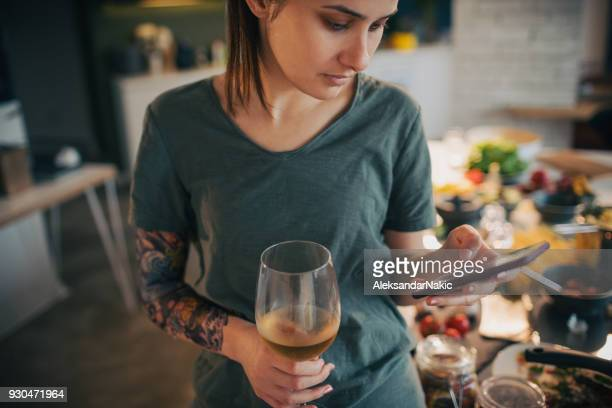 drinking wine and using smart phone while preparing a food - food and drink imagens e fotografias de stock