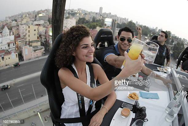Drinks are enjoyed as 22 men and women suspended 50 meters over a parking lot enjoy their meal at �Dinner in the Sky' on July 10 in Beirut where...