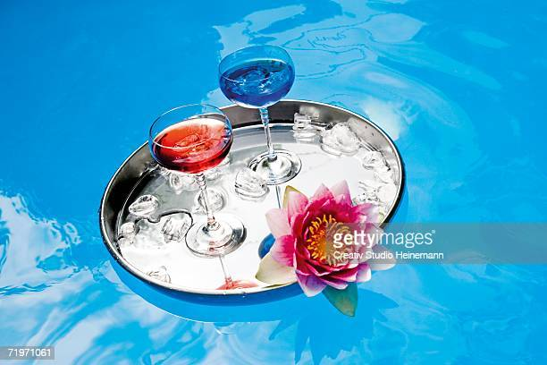 Drinks on tray floating in pool, elevated view