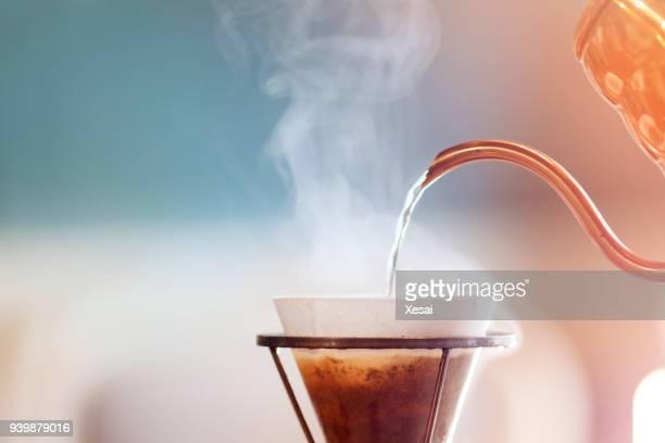 Filterkaffee, Barista gießt Wasser auf Kaffeesatz mit filter