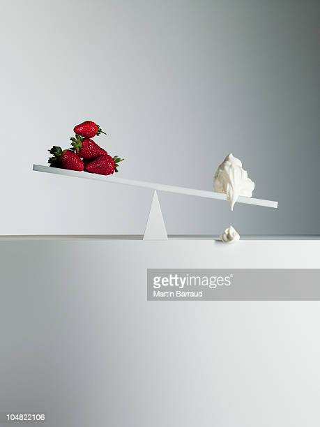 Dripping cream tipping seesaw with strawberries on opposite end