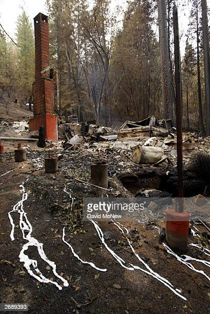 Drips of melted aluminum lie under a light rain at the ruins of 300 homes destroyed in the Old Fire along Hook Creek Road in the community of Cedar...