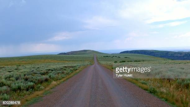 drive on gravel road in open plain summit steens mountain near malhuer wildlife refuge 20 - steens mountain stock pictures, royalty-free photos & images