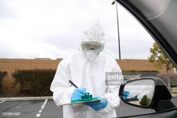 covid-19 drive through testing medical staff with clipboard eyes down - drive through stock pictures, royalty-free photos & images