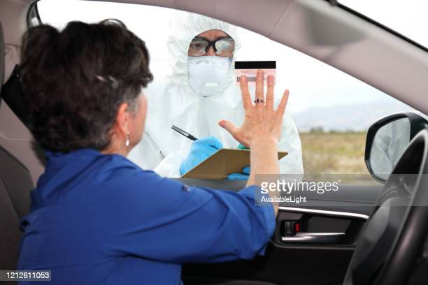 covid-19 drive through testing woman shows id - drive through stock pictures, royalty-free photos & images