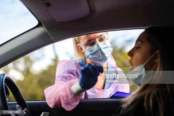 drive thru covid-19 testing with ppe medical staff throat swab - coronavirus australia stock pictures, royalty-free photos & images