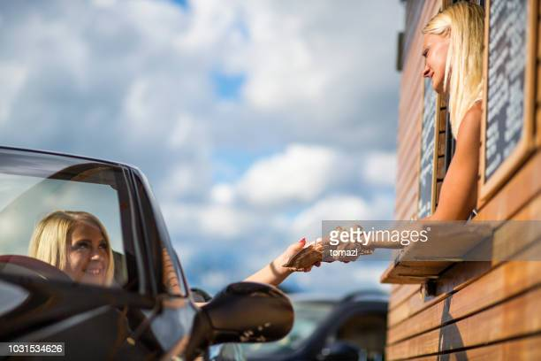 drive-in caffe female clerk with sandwich - drive through stock pictures, royalty-free photos & images