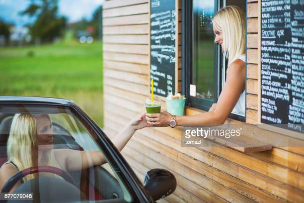 Drive-in caffe female clerk with smoothie