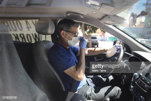 Driver adjusts his face mask as Uber and Lyft drivers with Rideshare Drivers United and the Transport Workers Union of America conduct a 'caravan...
