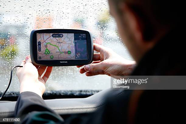 A driver adjusts his TomTom navigation system manufactured by TomTom NV as it sits on a vehicle windscreen in Manchester UK on Friday May 29 2015...