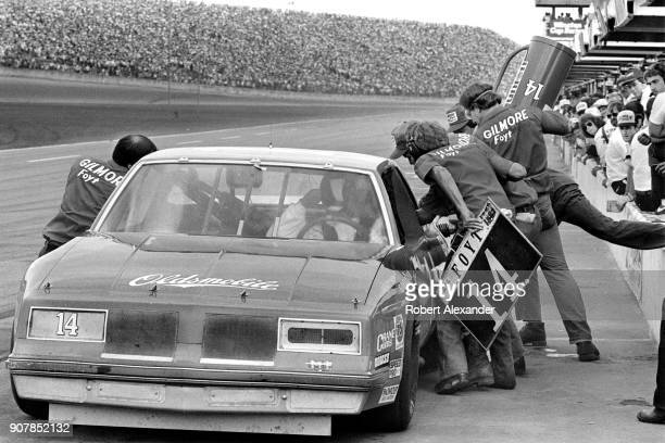 NASCAR driver AJ Foyt's crew add fuel to the racecar and confer with Foyt during a green flag pit stop during the 1984 Daytona 500 NASCAR race at...